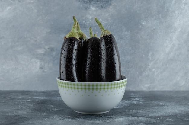 Organische rohe auberginen in der schüssel auf grauem hintergrund. nahansicht.