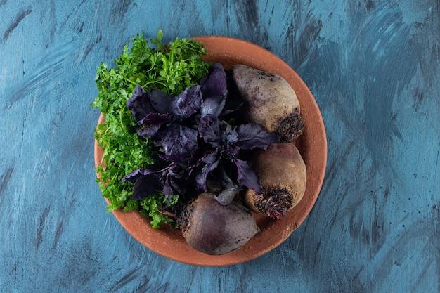 Organische rote-bete-wurzeln, dill und basilikumblätter auf keramikplatte.