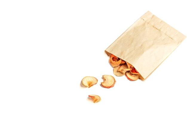 Organische selbst gemachte trockene fruchtchips in einem papier-eco satz auf weiß
