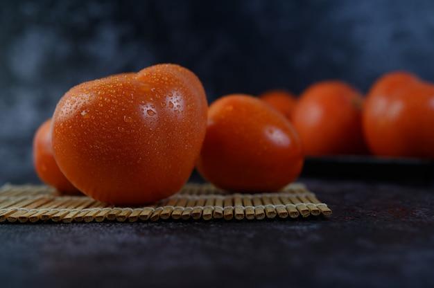Organische tomate mit wassertröpfchen im nahaufnahmemakro.