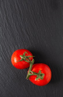Organische tomaten des lebensmittelkonzeptes auf schwarzem schieferbrett mit kopienraum