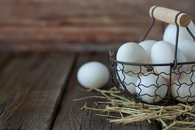 Organische weiße hühnereier im korb auf rustikalem hintergrund. platz für ihren text