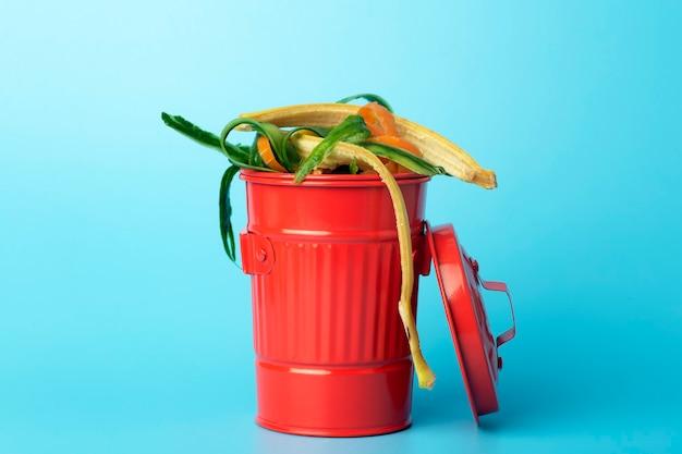 Organischer abfall in einem roten mülleimer. recycling und sortierung von müll, lebensmitteln und organischen abfällen.