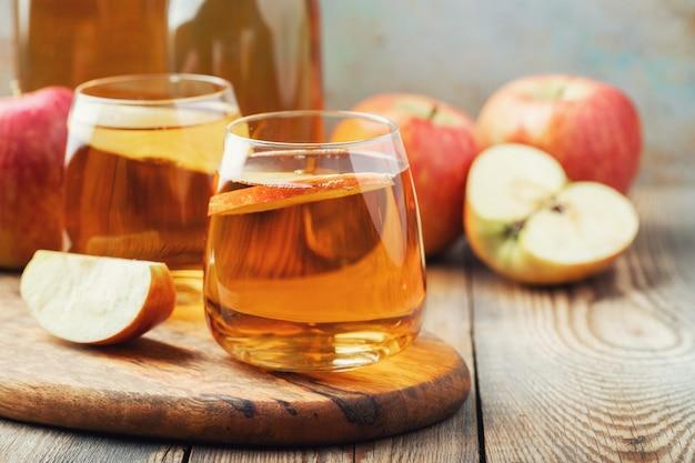 Organischer apfelwein oder saft auf einem holztisch. zwei gläser mit getränk und herbstlaub auf rustikalem hintergrund.