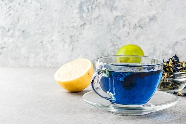 Organischer blauer schmetterlingserbsen-blumentee der gesunden getränke mit grauem konkretem hintergrund der kalke und der zitronen