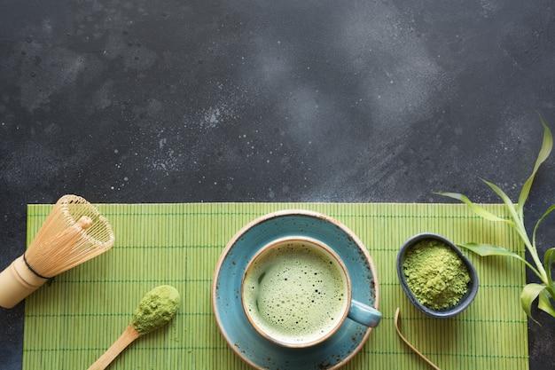 Organischer grüner matcha tee der zeremonie auf schwarzer tabelle. ansicht von oben. platz für text.