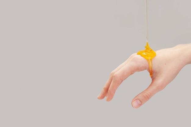 Organischer honig, der auf eine hand gießt
