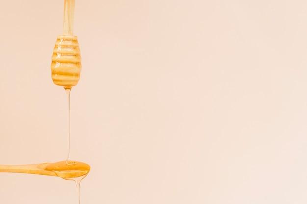 Organischer honig der nahaufnahme, der auf einen löffel gießt