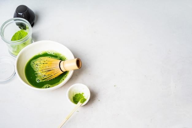 Organischer japanischer matcha-grüner tee, der prozess in einer schüssel mit werkzeugen chasen-bambus kocht, wischen