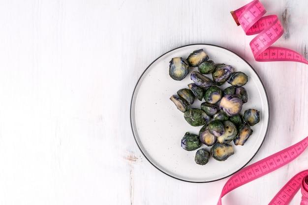 Organischer purpurroter rosenkohl gebraten auf platte
