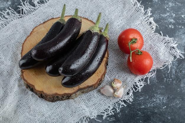 Organisches gemüse. lila auberginen auf holzbrett mit tomate und knoblauch.