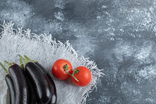 Organisches gemüse. lila auberginen mit tomate auf grauem hintergrund.