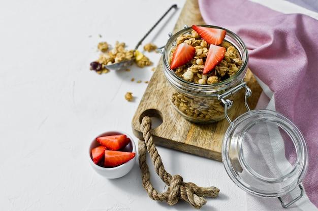 Organisches granola mit erdbeeren in einem glasgefäß.