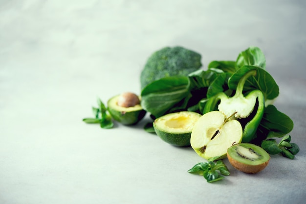 Organisches grünes gemüse und früchte auf grauem hintergrund.