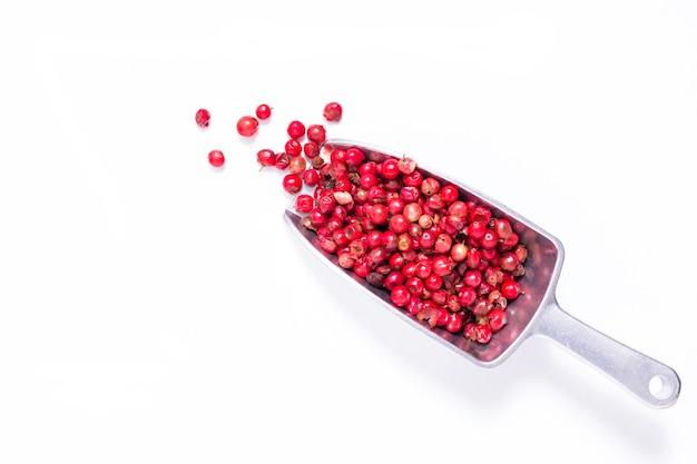 Organisches pfefferkorn oder rosa pfeffer in der eisenschaufel auf weißem hintergrund