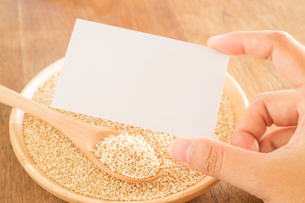 Organisches quinoakorn und hand auf visitenkarte