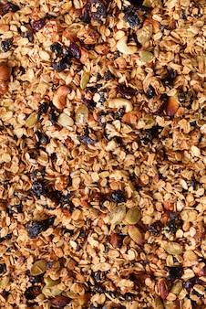 Organisches selbst gemachtes gebratenes granola mit nüssen und rasins auf backblech. essen zum frühstück. mahlzeithintergrund, granolabeschaffenheit