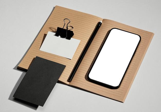 Organisierte anordnung von schreibwarenelementen mit smartphone mit leerem bildschirm