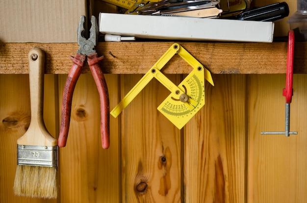 Organisierte werkzeugaufbewahrung. verschiedene alte werkzeuge hängen