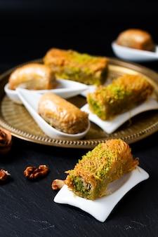 Orientalische arabische nachtischbaklava-walnüsse des lebensmittelkonzeptes und gerolltes kanafeh auf schwarzem schiefer verschalen