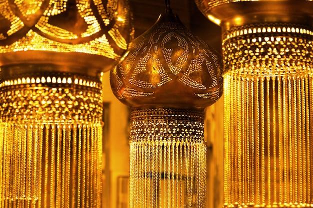 Orientalische hängende lampen der dunklen weinlese in einem goldenen glühen.