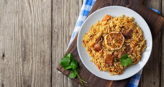 Orientalische küche. usbekischer pilaw oder plov aus reis und fleisch. rustikaler hölzerner hintergrund.
