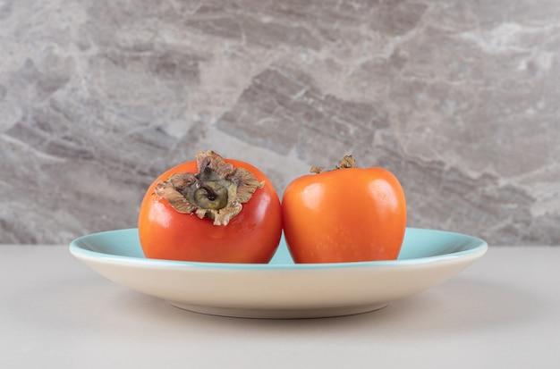 Orientalische persimone auf einer blauen platte auf marmor
