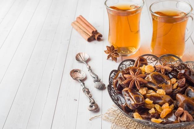 Orientalische süßigkeiten, datteln mit getrockneten früchten und rosinen, zimt und sternanis in einem teller