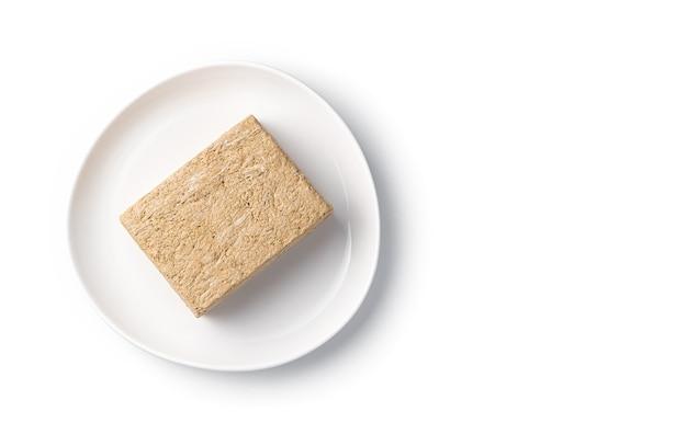 Orientalische süßigkeiten, halva auf einem weißen teller. draufsicht, isoliertes objekt.