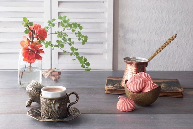 Orientalischer kaffee, der in einer traditionellen türkischen kaffeekanne aus kupfer gekocht und in einer passenden tasse serviert wird