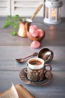 Orientalischer kaffee, der in einer traditionellen türkischen kupferkanne gekocht und in einer passenden tasse serviert wird