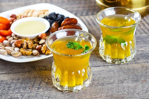 Orientalischer tee mit minze, honig, nüssen und getrockneten früchten auf holztisch. ramadan trinken