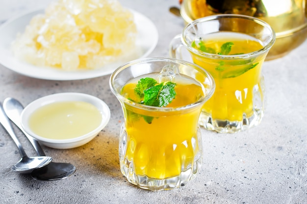Orientalischer tee mit minze, honig und orientalischen süßigkeiten auf grauem betontisch. ramadan trinken