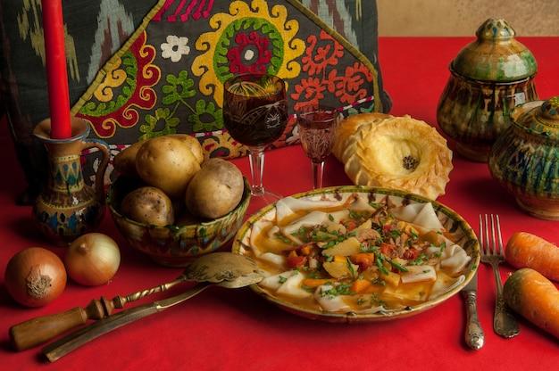 Orientalisches gericht aus teig und gemüse auf einer roten tischdecke tilllife aus einem orientalischen teiggericht