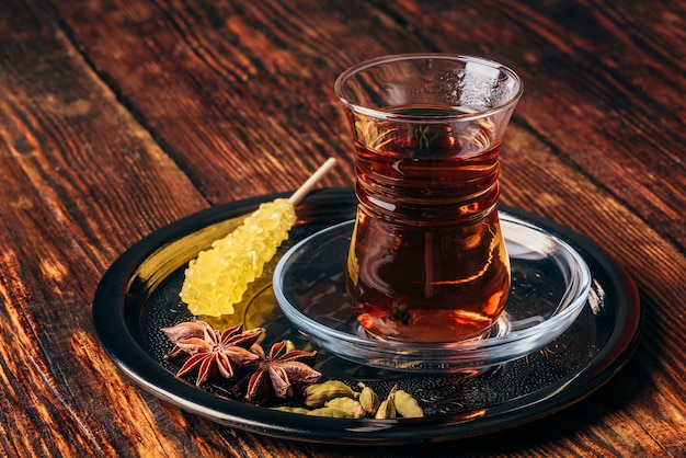 Orientalisches glas mit gewürztee und navad auf metalltablett über holzoberfläche