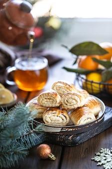 Orientalisches nachtisch gata mit einer tasse tee und tangerinen auf einem holztisch