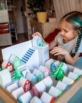 Origami adventskalender. nettes mädchen, das winzige papierhäuser mit nummer betrachtet
