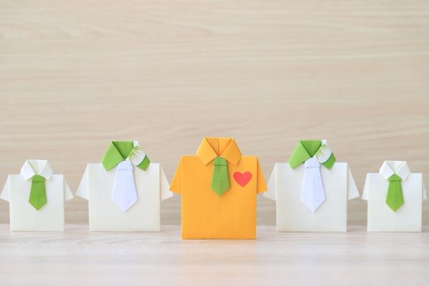 Origami gelbes hemd mit der bindung, die unter kleinem gelbem hemd auf wooder hintergrund führt