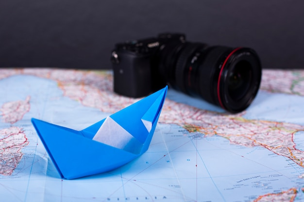 Origami handgemachtes papierschiff-papierschiff des reiseurlaubskonzeptes auf karte nahe italien schließen nahaufnahme studion schuss