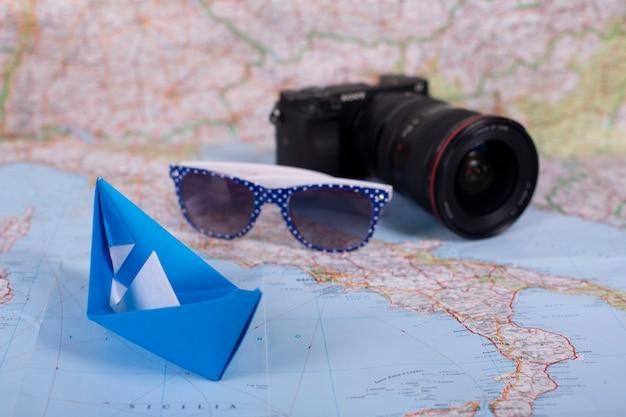 Origami handgemachtes papierschiff papierschiff des reiseurlaubskonzepts mit kamera und sonnenbrille auf karte nahe italien nah oben