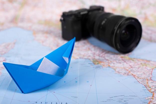 Origami handgemachtes papierschiff papierschiff und kamera des reiseurlaubskonzeptes auf karte nahe italien schließen nahaufnahme studion schuss