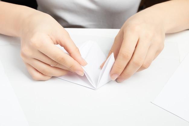 Origami ist eine alte chinesische kunst des papierfaltens. weibliche hände machen eine figur