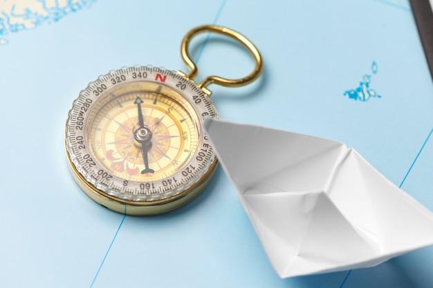 Origami papierschiff auf einer karte. führungs- und reisekonzept