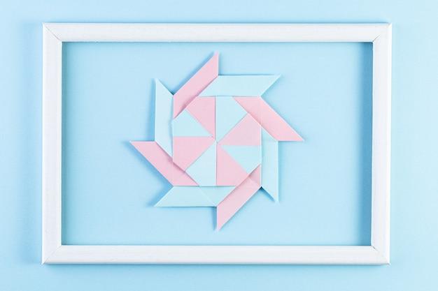 Origami-stern. hergestellt aus quadratischen papierbögen und weißem holzrahmen.
