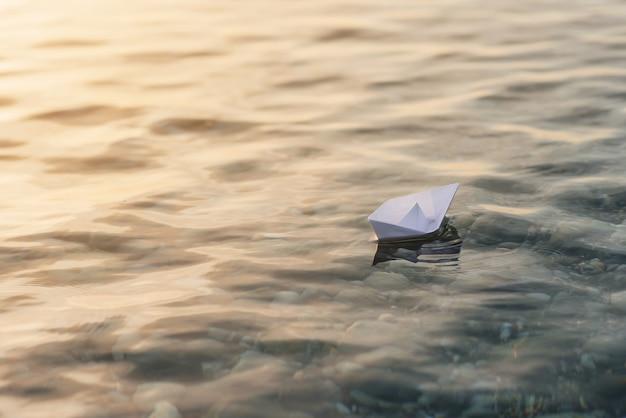 Origami weißes papierboot auf blauem tiefem wasser.