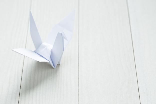 Origamipapiervogel auf weißer tabelle