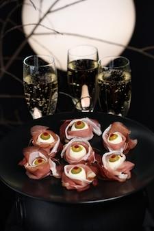 Original halloween snacks. augäpfel aus schinken mit mozzarella, oliven gefüllt mit rotem pfeffer