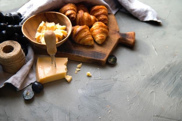 Original leckere französische croissants mit käse und trauben auf dem holztisch. butterflocken-wiennoiserie-brötchen mit markanter halbmondform. käse in schüssel, messer, schneidebrett als hintergrund.