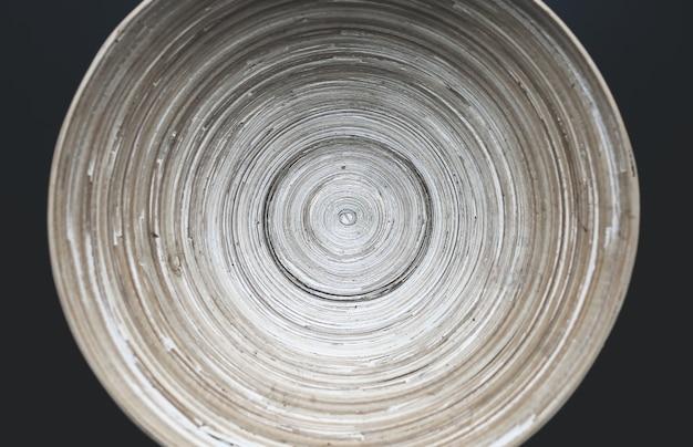 Originaler holzteller mit durchgehenden linien auf dem schwarzen tisch. organisches, natürliches schalenmaterial mit ewigen linien. umweltfreundliches foto. hellbeiges minimalistisches layout.