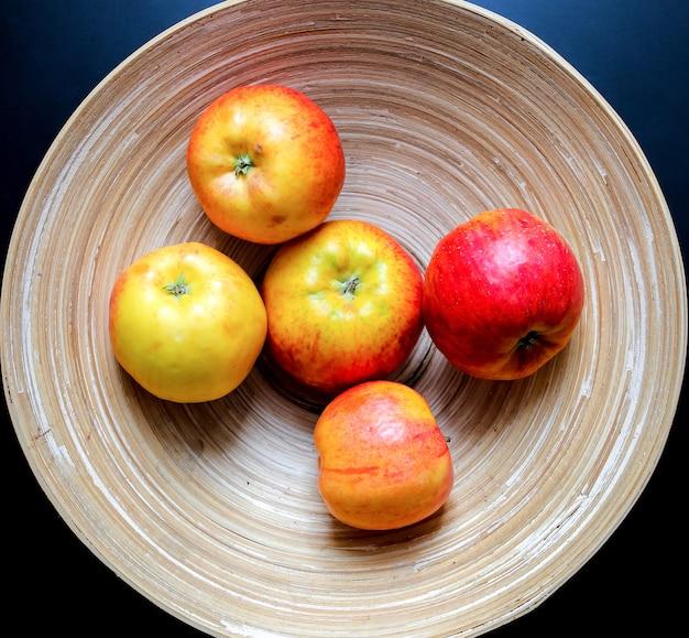 Originaler holzteller mit durchgehenden linien und fünf äpfeln auf dem schwarzen tisch. organisches, natürliches schalenmaterial mit ewigen linien. umweltfreundliches obstfoto. hellbeiger minimalismus flach.